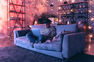 Teenager in bandana watching his favorite movie in cozy atmosphere.