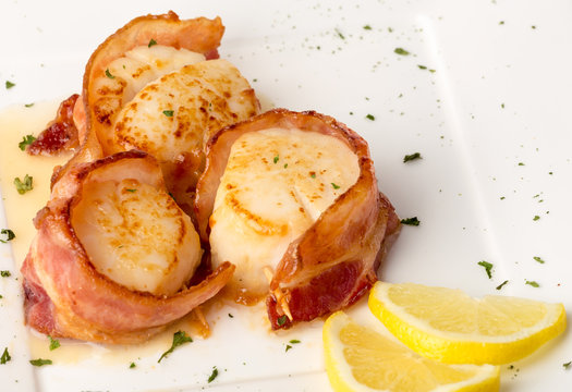 Bacon Wrapped Scallops on White Plate with Lemon Slices and Green Garnish
