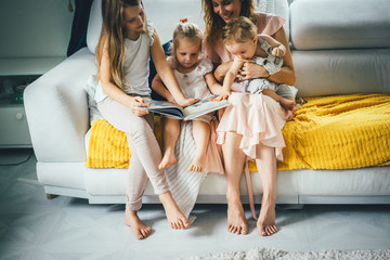 mother with three children reading a book in a homely atmosphere, sharing time with parents and children. mother, two daughters and a little son.
