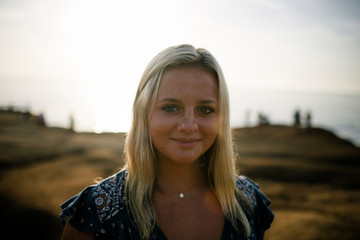 Portrait of smiling woman with blond hair standing on cliff against sea during sunset