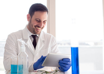 Biologist analyzing tests on tablet in laboratory