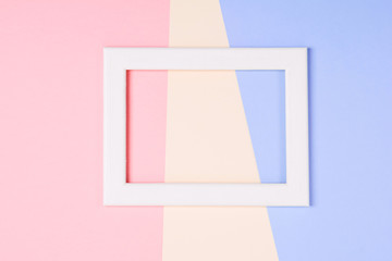 White wooden frame over pastel colorful paper background