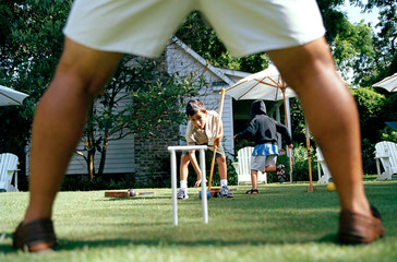 Portrait of a young boy playing croquet with family in the garden.