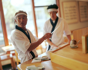 Two Japanese chefs preparing for diners in a traditional restaurant.