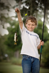 Young boy holding a fish on the end of a fishing line.
