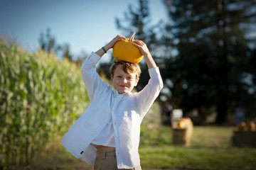Portrait of a young boy carrying a pumpkin on his head.