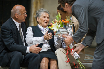 Happy senior woman sitting with her husband and mid-adult daughter being presented a bouquet of flowers from her son.