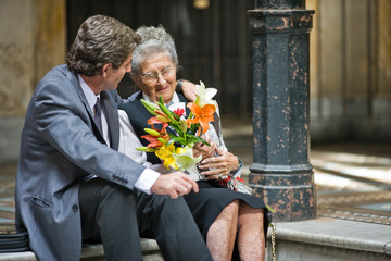 Senior adult woman sitting being embraced by her mid-adult son and holding flowers in a foyer.