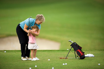 Senior woman teaching her young granddaughter how to swing a golf club on a golf course.