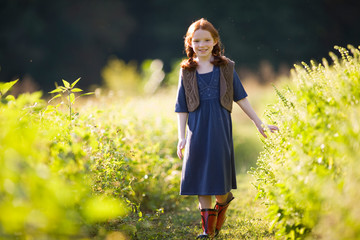 Portrait of a young girl walking through a field.