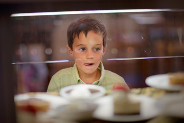 Young boy licking his as he looks through the window of a food cabinet.