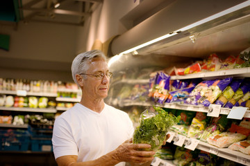 Mature man holding up a lettuce at a grocery store.