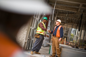 Mature male construction worker shaking hands with a mid-adult co-worker on a building site.