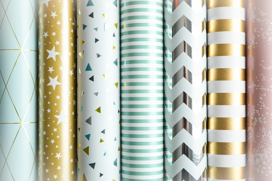 Rolls of festive wrapping paper as background. Top view