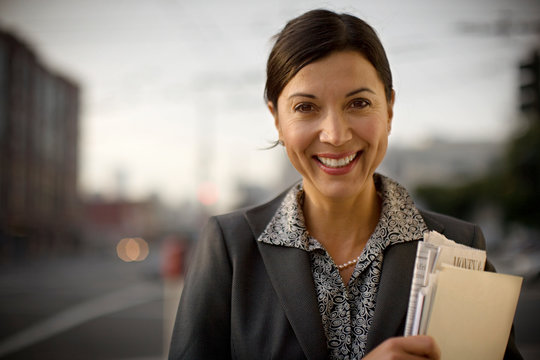 Portrait of a smiling mid-adult businesswoman holding a folder of documents.