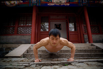 Young adult man doing press ups outside a building.