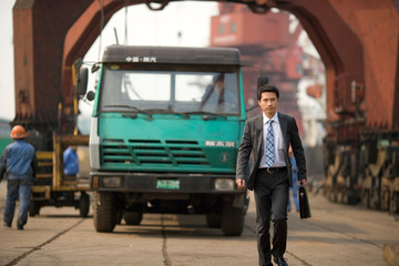 Young adult businessman walking on a wharf.