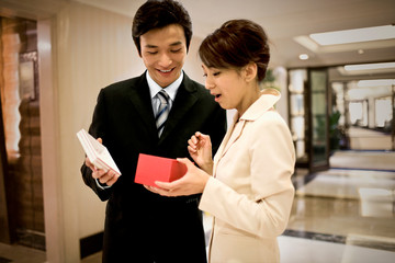 Young adult businessman giving a gift to his girlfriend in a lobby.