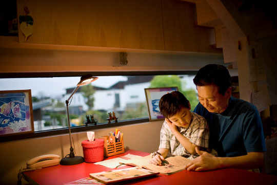 Mature man sitting reading with his son.