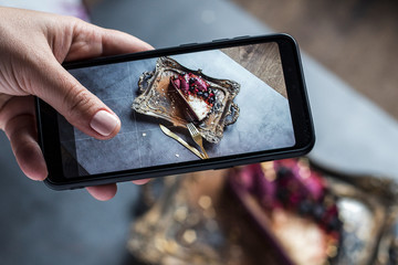 female hand with pink manicure photographs on phone piece of cake on a gold tray