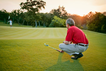 Mature man measures distance on the ground with his club as he enjoys himself on the course at sunset.