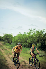 Adventurous young couple have a friendly race on their mountain bikes along a country lane.