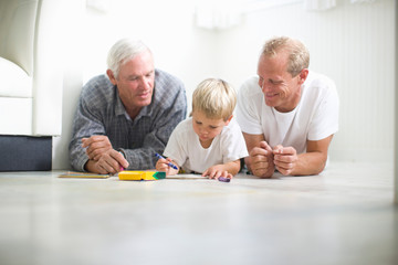 Young boy sitting on the floor with his grandfather and father while drawing with crayons.