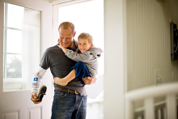 Smiling father holding his young son in the doorway of their home.