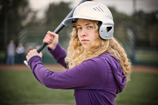 Portrait of a confident young woman wearing a helmet and holding a baseball bat.