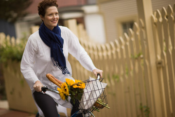 Woman riding a bicycle with sunflowers in the basket