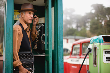 Mature man wearing a hat while listening on the phone in a public phone booth holding a typewriter.