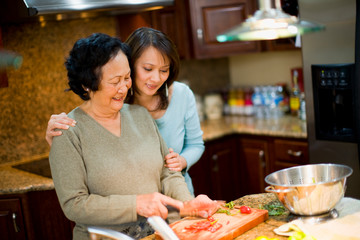 Woman hugging mother as she cuts tomatoes