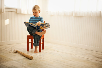 Little boy sitting on a chair reading a book