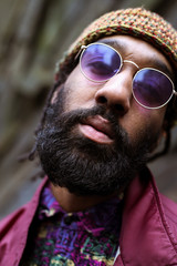 Close up of adult with beard and purple tinted sunglasses