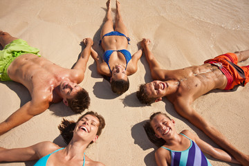 Five laughing people holding hands while lying in the shape of a star on a sandy beach.