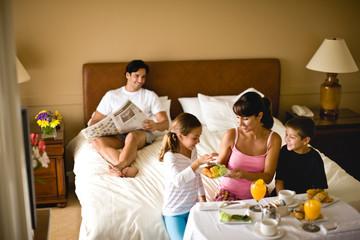 Family enjoying breakfast in bed in hotel room.