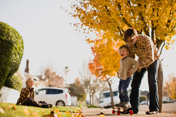 Father helping son balance on skateboard while brother watches from lawn.