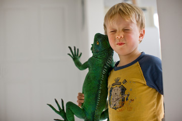 A young boy holding a large toy lizard.