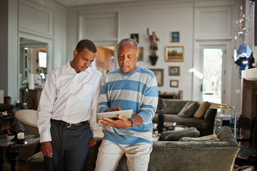 Mature man showing a digital tablet to his teenage son.