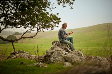Middle aged man texting on a cell phone while sitting on a rock in a rural field.