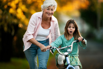 Little girl learning to ride her bicycle with the help of her grandmother.