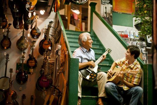 Smiling senior man playing guitar with his teenage grandson.