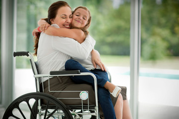 Senior woman in a wheelchair,  receiving a visit from her granddaughter.