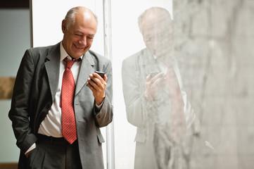 Senior businessman receiving good news on his iphone.