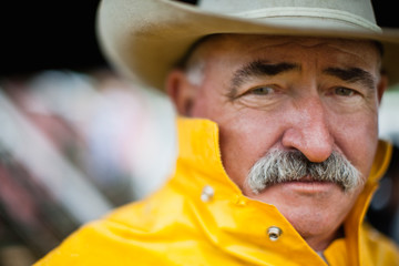 Portrait of mature man wearing cowboy hat and rain jacket.