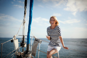 Portrait of smiling mid-adult woman standing on boat deck, holding cell phone.