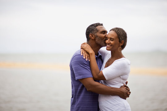 Mature man kissing his wife on the beach.