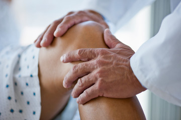 Doctor's hands examining a patient's knee.