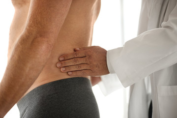 Doctor examines a young man's lower back.