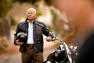 Portrait of a senior man and his motorcycle.